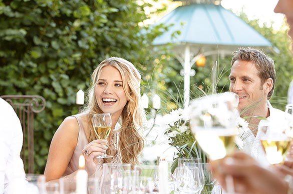 Gartenparty Portrait junges Paar im Garten vor Hecke in Sommersonne