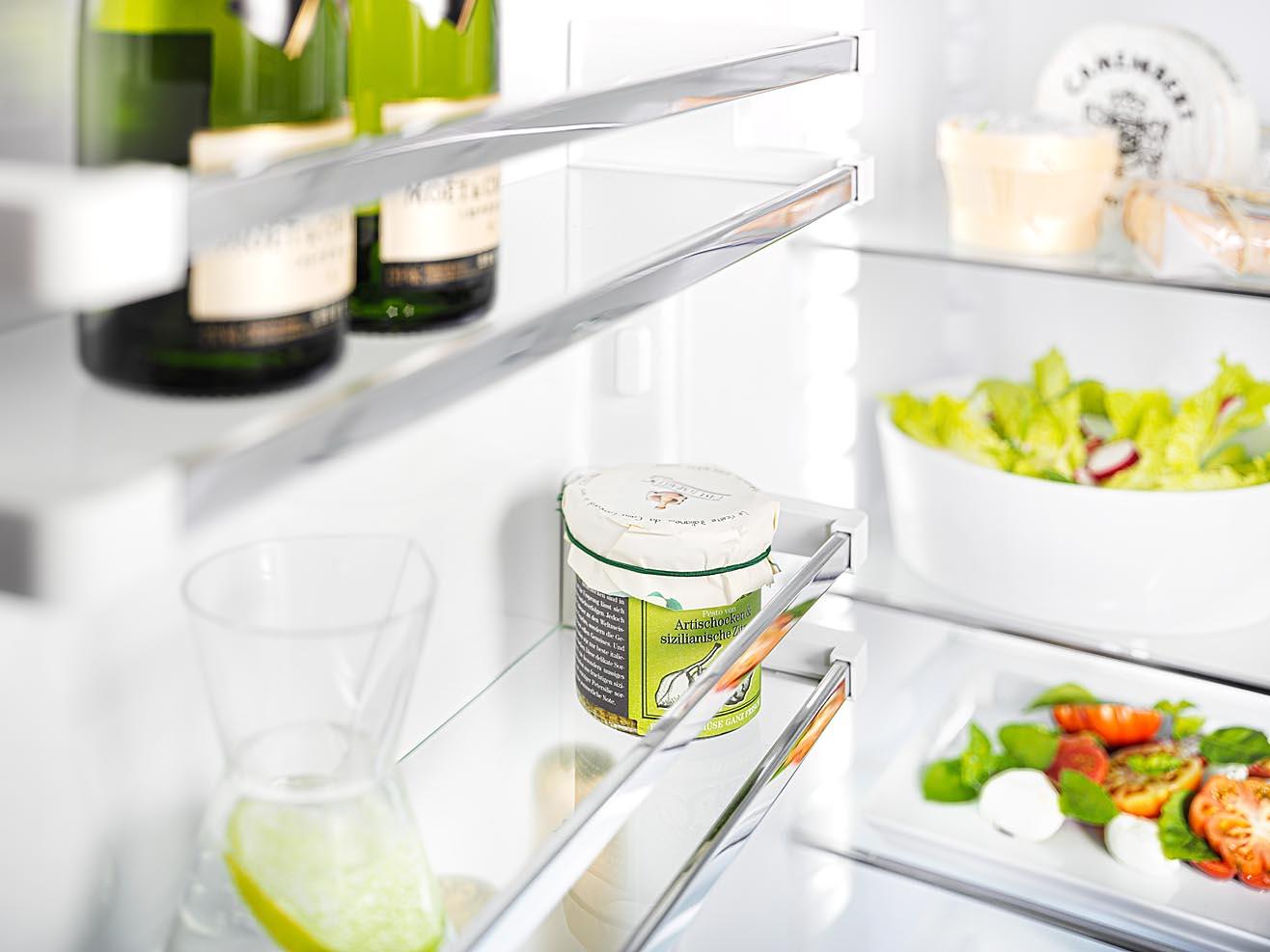 Foto eines Kühlschrankdetails mit Lebensmitteln. Glasborde Chrom-Reeling fotografiert mit Fachkamera und bewusster Schärfe-Verlagerung
