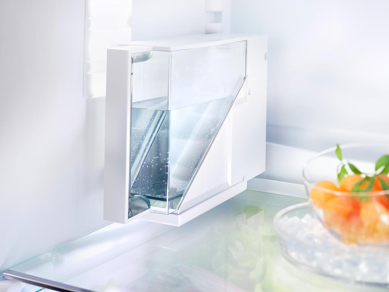 Foto eines Kühlschrankdetails mit Lebensmitteln. Wassertank für Icemaker fotografiert mit Fachkamera und bewusster Schärfe-Verlagerung