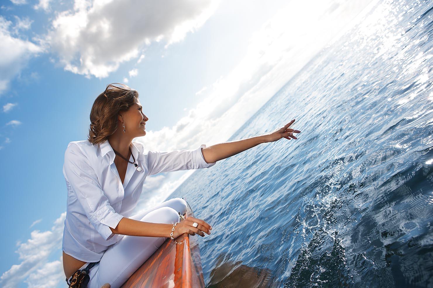 Weibliches Model auf einem Segelboot spritzt mit der Hand im Wasser