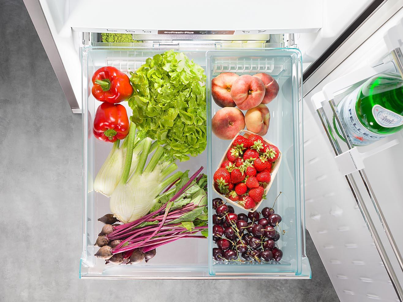 Foto eines Kühlschrankdetails mit Lebensmitteln. Schublade mit Vollauszug fotografiert mit Fachkamera aus spannender Perspektive