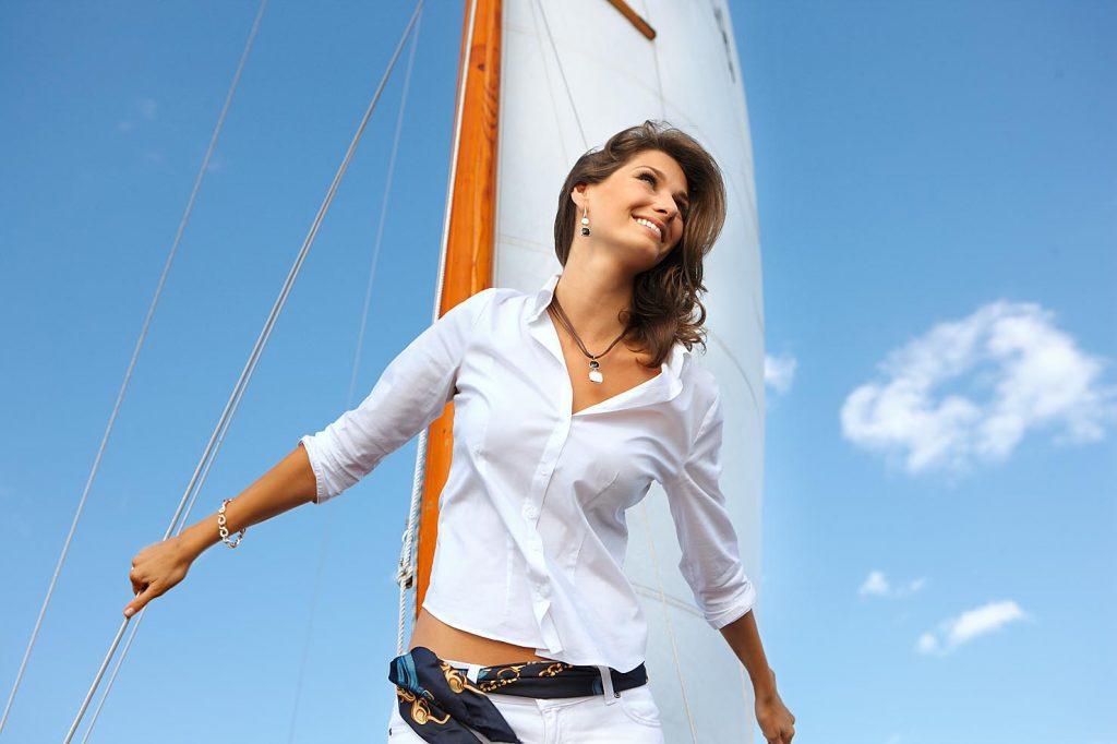Modelfotografie auf einem Segelboot mit Model vor Mast und blauem Himmel